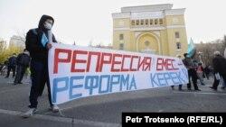 """Билік келісім берген бейбіт жиынға келген адамдар """"Репрессия емес, реформа керек!"""" деген жазу ұстап тұр. Алматы, 31 қазан 2020 жыл."""