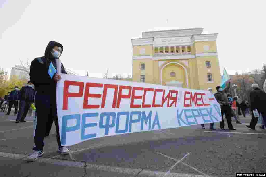 """Алматыдағы билік келісім берген митингіде """"Реформа емес, реформа керек!"""" деген жазу ұстап тұр. 31 қазан 2020 жыл."""