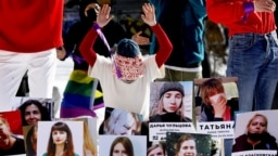 An activist takes part in a flash mob with photographs of women imprisoned since the presidential election on August 9, 2020, as they protest against police violence in Minsk on February 14.