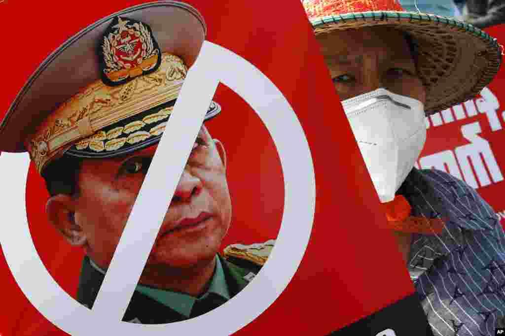 Протестувальник тримає плакат із перекресленим зображенням головнокомандувача, старшого генерала Мін Аун Хлаін, він є також головою Державної адміністративної ради, під час мітингу проти перевороту перед будівлею Економічного банку М'янми в Мандалаї, 15 лютого 2021 року