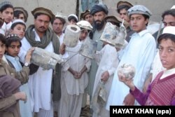 Hayatullah Khan's photo of villagers with missile shrapnel from a U.S. drone strike in North Waziristan that reportedly killed senior Al-Qaeda leader Abu Hamza Rabia in December 2005.