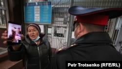Полицейский и женщина в управлении полиции Медеуского района. Алматы, 14 ноября 2020 года.