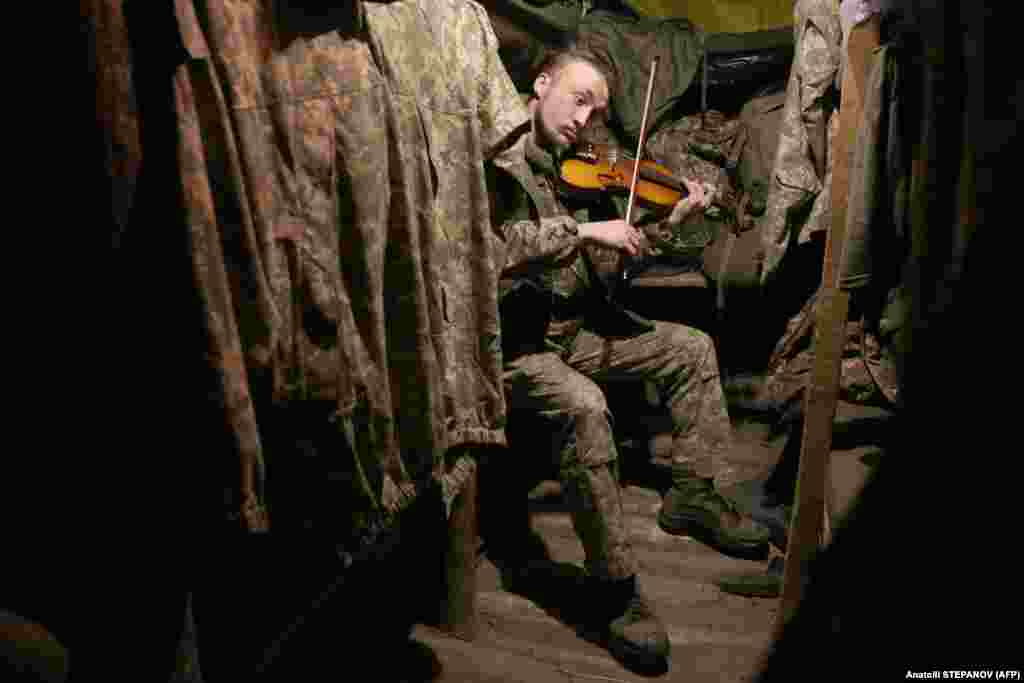 A Ukrainian serviceman plays the violin in a dugout on the front line with Russia-backed separatists in the Donetsk region. (AFP/Anatolii Stepanov)