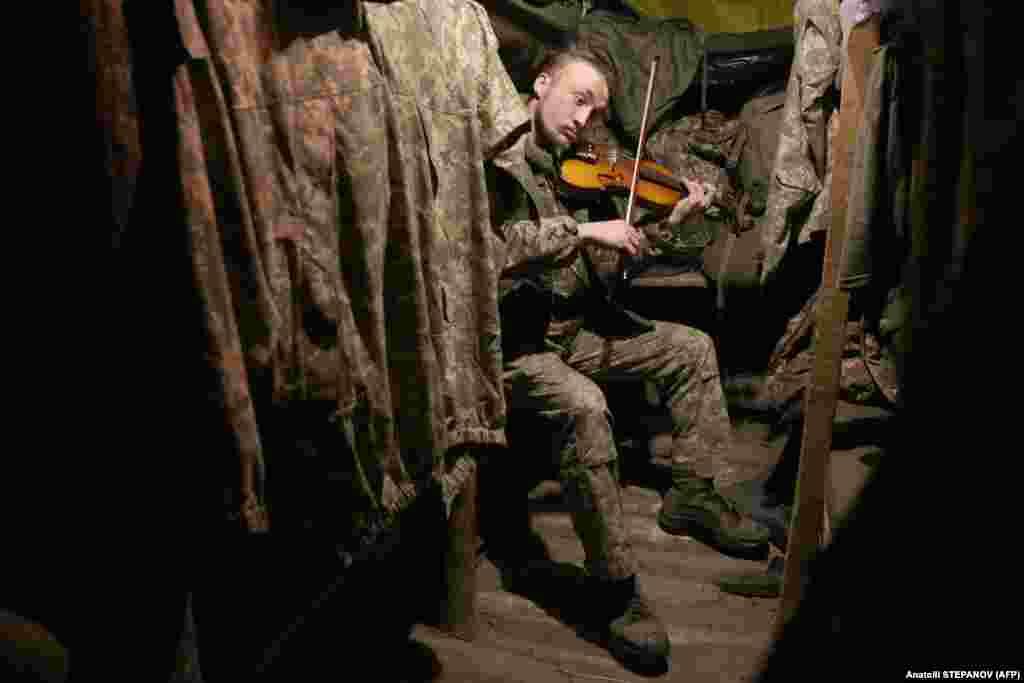 Ukrajinski vojnik svira violinu u rovu na prvoj liniji s separatistima koje podržava Rusija u regiji Donjeck. (AFP / Anatolij Stepanov)