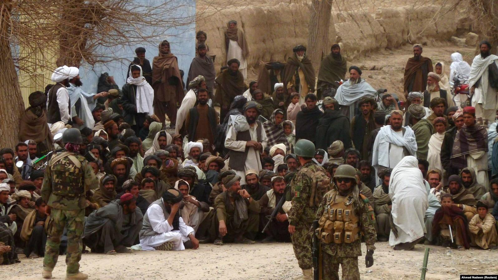 Afganistanska vojska drži stražu dok se Afganistanci okupljaju oko američke baze u Panjawi distriktu u Kandahar provinciji nakon ubistva koje se desilo 11. marta 2012.