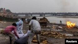 Коронавирусnfy (COVID-19) өлгөн адамдын сөөгүн өрттөө алдында. Ганг дарыясынын жээги. Уттар-Прадеш штаты. Индия. 6-май, 2021-жыл.