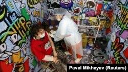 Қазақстандық мамандар коронавирус инфекциясына (COVID-19) қарсы әзірлеген QazCovid екпесін сауда орталығында ұйымдастырылған вакцина салу орнында қабылдап отырған адам. Алматы, 27 сәуір 2021 жыл.
