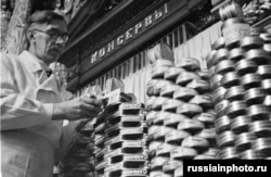 A store worker stacks cans of sardines in 1950.
