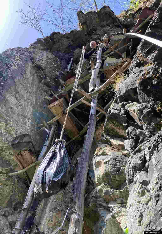 Путкарадзе спускает мешок с урожаем сыну, который ждет внизу с ведром, чтобы снести соты с горы. Сбор урожая проводится только раз в год