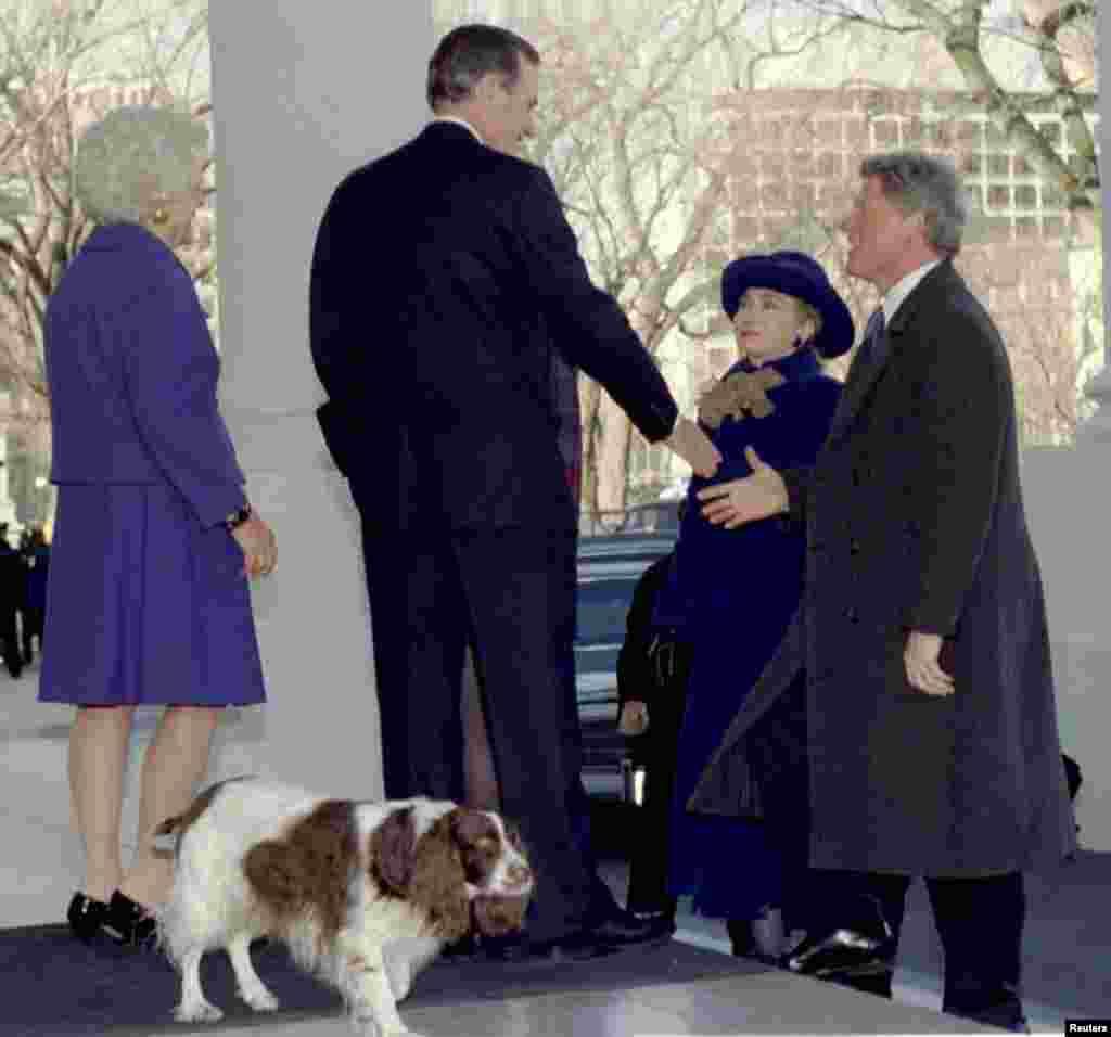 20 января 1993 года. Избранный президент Билл Клинтон (справа) вместе с женой Хиллари Клинтон здоровается с 41-м президентом Джорджем Бушем (слева) и первой леди Барбарой Буш во время визита в Белый дом. Позади Бушей, на переднем плане – их пес Милли
