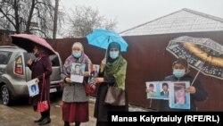 Женщины стоят на улице Байтасова с фотографиями остающихся в Синьцзяне родственников, в 50-й день пикетов у консульства Китая. Алматы, 29 марта 2021 года.