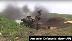 An Armenian serviceman fires a cannon toward Azerbaijani positions close to the so-called Line of Contact on October 2.