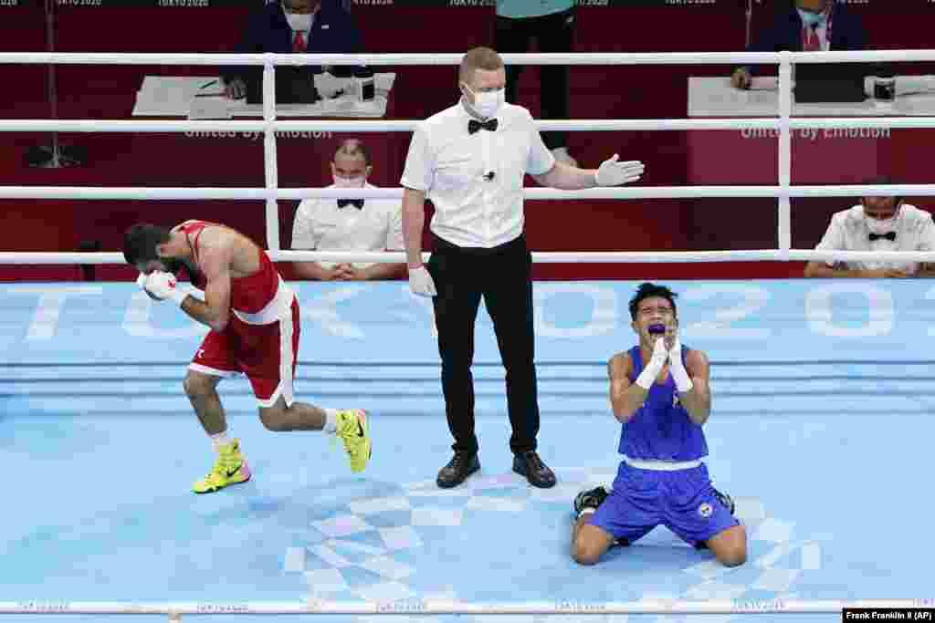 Расстроенный Шахобидин Зоиров из Узбекистана и радостный Карло Паалам из Филиппин, который победил в четвертьфинальном поединке мужчин по боксу в легком весе 52 кг. Токио, 3 августа 2021