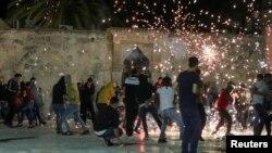 Palestinci reaguju dok izraelska policija vatrenim granatama puca tokom sukoba u kompleksu u kojem se nalazi džamija Al Aksa