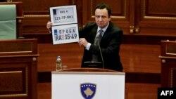 Kryeministri i Kosovës, Albin Kurti, tregon targat e përkohshme të makinave në Kosovë dhe Serbi gjatë një seance parlamentare në Prishtinë, 20 shtator 2021.