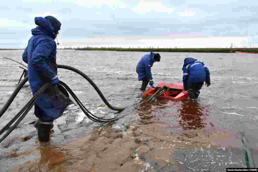 Employees of Russia's state-owned oil pipeline monopoly Transneft take part in a cleanup operation following May's massive fuel spill in the Ambarnaya River outside Norilsk.