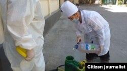 Yakkasaroy SEOM xodimi Xolisxon Umarova niqob, qo'lqop va oq xalat bilan aholi punktlarini dezinfektsiya qilmoqda, iyulь, 2020
