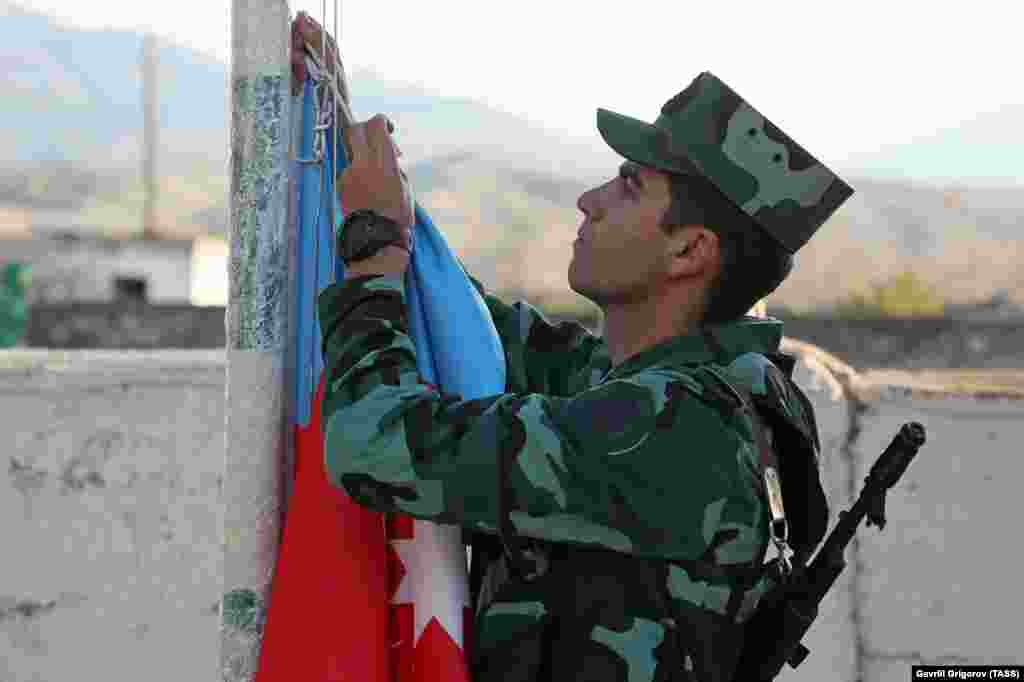 An Azerbaijani soldier hoists his country's flag during a ceremony in the village of Mincivan, which was recently taken from Armenian forces.