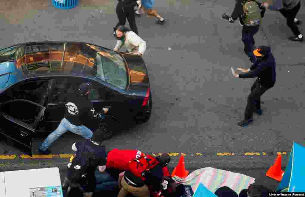 Водій, який вирішив проїхати охопленою протестом вулицею, виходить із автомобіля з пістолетом у руці. Поруч намагаються надати допомогу протестувальнику, якого він, ймовірно, щойно поранив. Той чоловік намагався витягти водія із автівки. У подальшому водій здався поліції. Заворушення у Сіетлі через смерть афроамериканця Джорджа Флойда, штат Вашингтон, США. 7 червня 2020 року