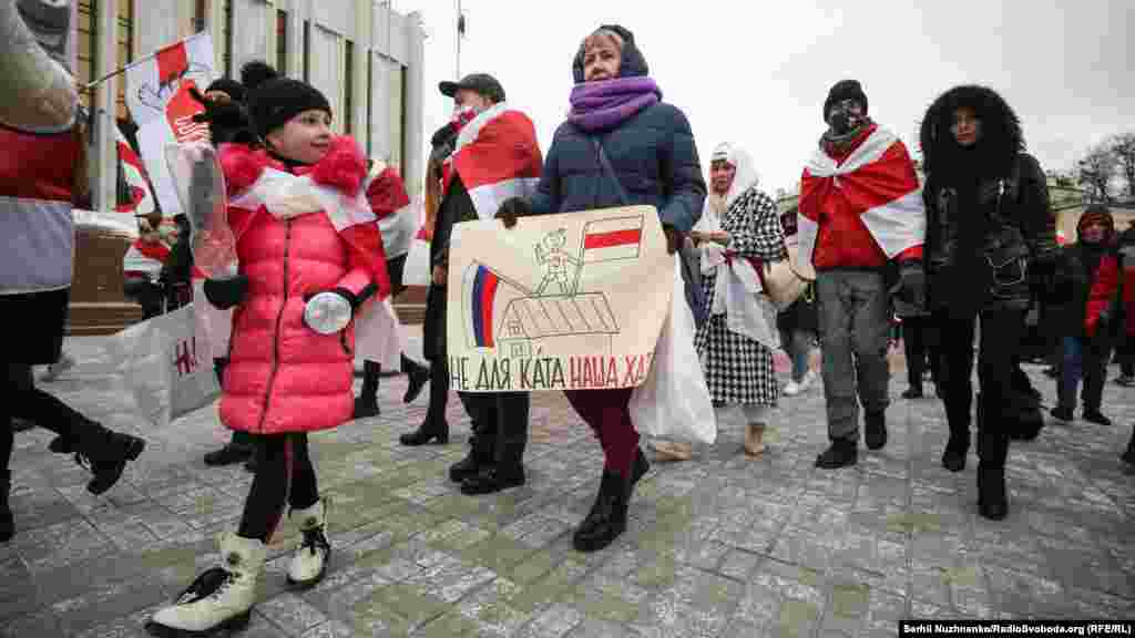 People march with the red and white colors of Belarus's pro-democracy protesters in a show of solidarity in Kyiv on February 7. (RFE/RL /Serhii Nuzhnenko)