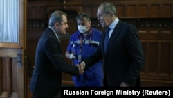 RUSSIA -- Russian Foreign Minister Sergei Lavrov greets his Azeri counterpart Ceyhun Bayramov, as a COVID-19 medic is ready to measure temperature, in Moscow, August 26, 2020