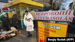 Локалните жители покрај рекламниот постер на унгарски јазик во Берегове, мал град во западна Украина, на 15 ноември 2017 година