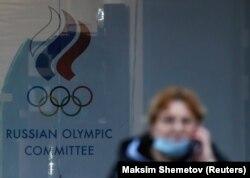 Egy járókelő az Orosz Olimpiai Tanács címere előtt. 2020. november 2.