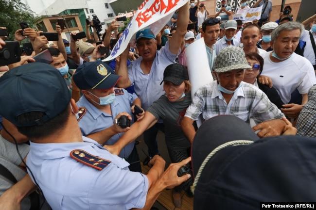 Полицейские пытаются отобрать плакаты у участников митинга. Алматы, 6 июля 2021 года