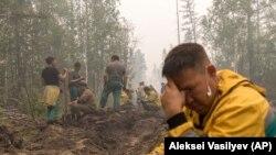 Сотрудники «Якутлесресурса» роют противопожарный ров для тушения лесного пожара возле села Магарас в 87 км к западу от Якутска Дальний Восток России, 18 июля 2021 года