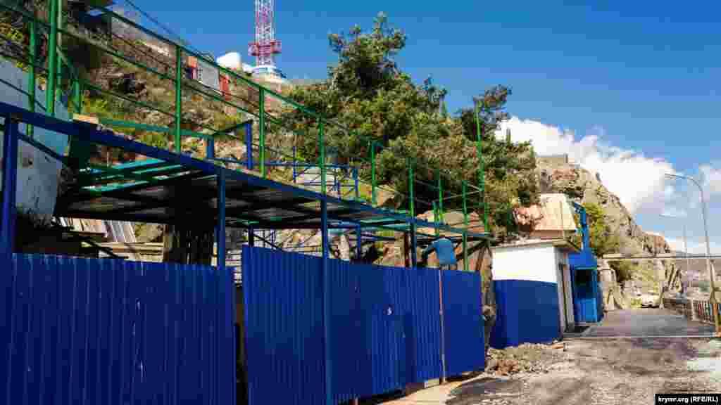 Робочий чистить від сміття гірський схил за будівельним парканом