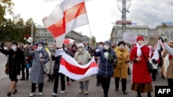 Belarusian pensioners carrying banned white-red-white flags and flowers parade through the streets of Minsk during a rally to demand the resignation of authoritarian leader Alyaksandr Lukashenka and a new fair election on October 19.