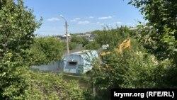 Строительный вагончик и экскаватор на улице Кокчетавской