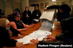 Дауыс беру аяқталғаннан кейін сайлау жәшігіндегі бюллетеньдерді төгіп жатқан сайлау комиссиясы. Бішкек, Қырғызстан, 10 қаңтар 2021 жыл.