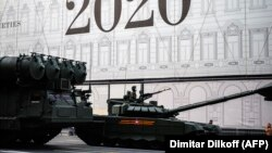 A Russian Army soldier rides a T-90 tank along a street prior to a rehearsal for a Victory Day parade in Moscow on June 17.