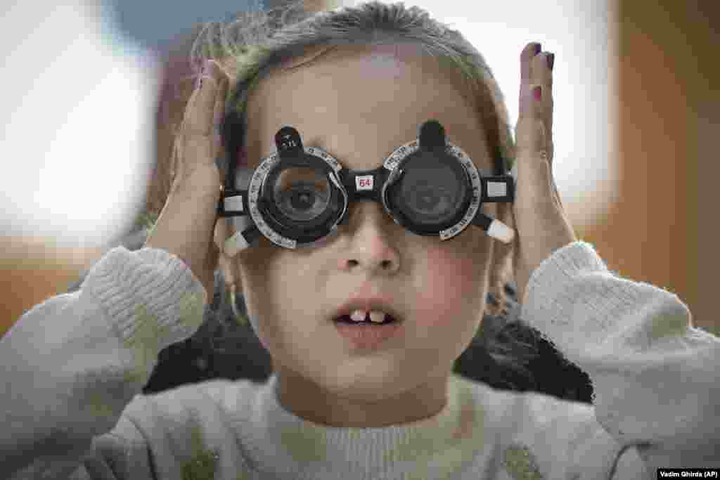 A little girl adjusts her testing glasses during an eyesight examination in Nucsoara, Romania.