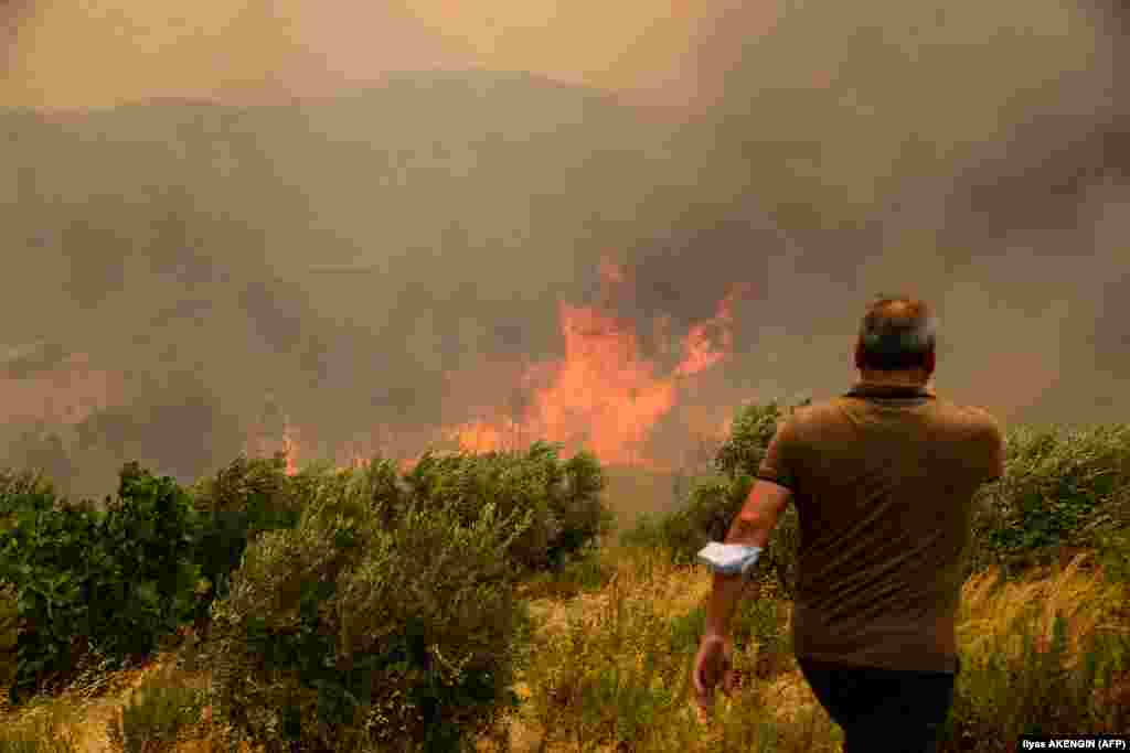 People extinguish bushes in flame during a massive forest fire which engulfed a Mediterranean resort region on Turkey's southern coast near the town of Manavgat, on July 29, 2021.