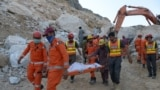 Army rescuers move the body of a miner from the site after a rockslide at a marble mine in the mountainous Mohmand district of Khyber Pakhtunkhwa Province.