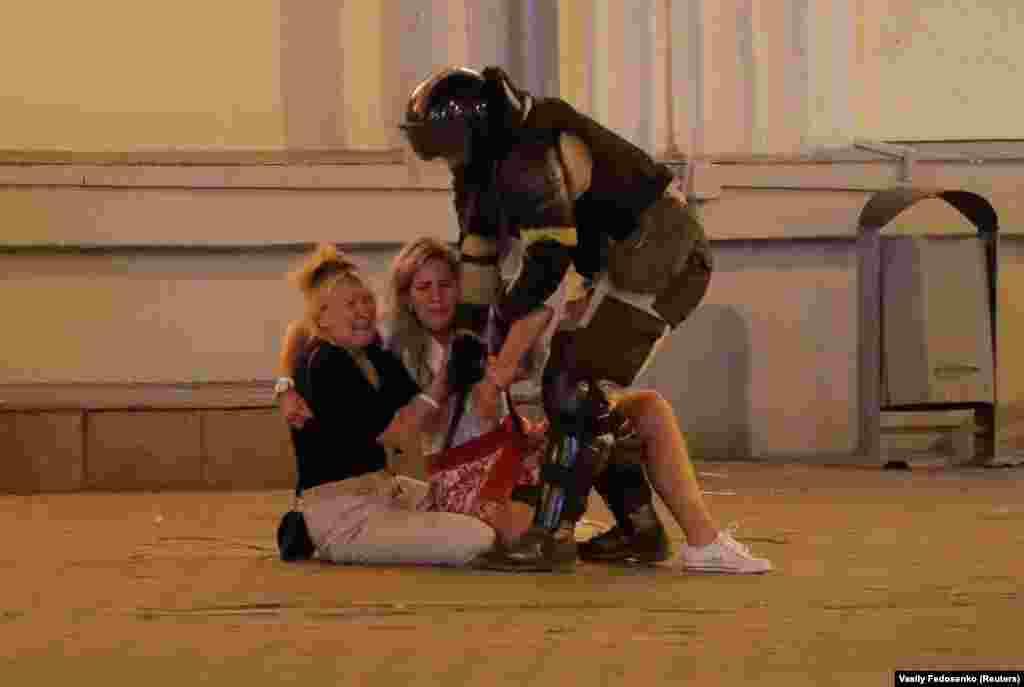 Two women cower in fear as a riot policeman approaches in Minsk.