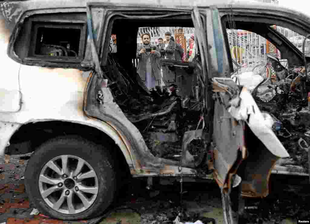 An Afghan journalist films a damaged vehicle at the site of a blast in Kabul on December 20.