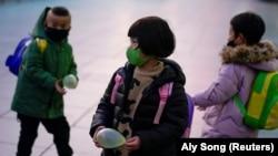 Дети в масках на перроне вокзала в Шанхае. 5 марта 2021 года.
