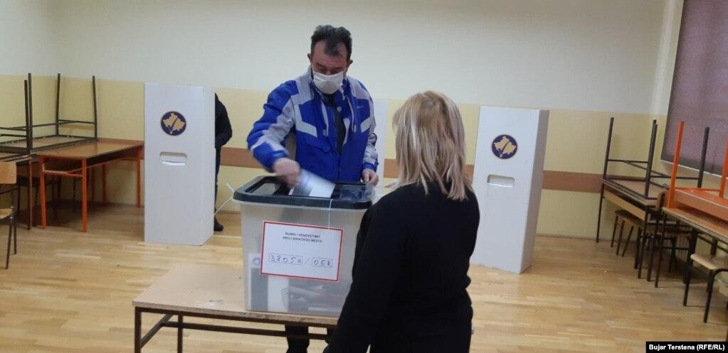 Një votues me maskë mbrojtëse duke votuar në Mitrovicën Veriore.