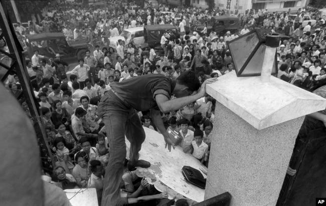 Вьетнамцы пытаются проникнуть на территорию американского посольства в Сайгоне, надеясь попасть на вертолеты, эвакуирующие американских граждан. 29 апреля 1975. Многие комментаторы сравнивают эвакуацию из Сайгона с эвакуацией из Кабула