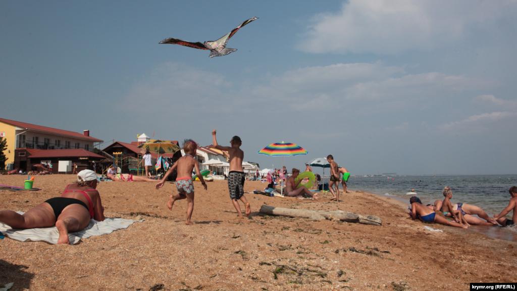 Дети запускают воздушного змея на «Золотом пляже» в Феодосии. Как проходили последние дни августа на берегу Черного моря в Феодосии – в фоторепортаже Крым.Реалии
