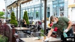 Felszolgáló fertőtlenítővel tisztítja egy étterem teraszán az egyik asztalt Nyíregyházán a Dózsa György utcában, 2020. május 4-én