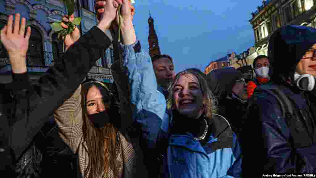 """Demonstrators in Kazan, the capital of the republic of Tatarstan, hand out flowers and shout, """"We come in peace."""""""