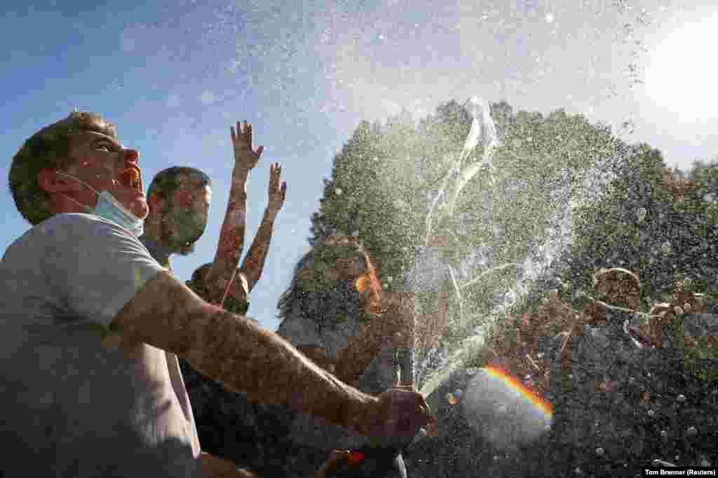 Люди святкують після того, як ЗМІ оголосили, що кандидат у президенти США Джо Байден виграв президентські вибори 2020 року, на Black Lives Matter Plaza біля Білого дому у Вашингтоні