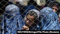 Афганские женщины ждут бесплатной пшеницы, подаренной афганским правительством во время карантина, на фоне опасений по поводу коронавирусной болезни (COVID-19) в Кабуле, Афганистан, 21 апреля 2020 г.