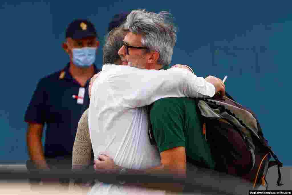 Люди обнимаются после рейса из Кабула, прибывшего в столицу Италии Рим 16 августа