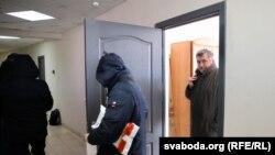 Старшыня БАЖ Андрэй Бастунец выходзіць з офісу арганізацыі зь сілавікамі пасьля ператрусу