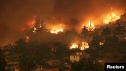 Пламени јазици во близина на куќите во селото Гувес, на островот Евија, Грција, 8 август 2021 година.